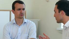 Δύο επιχειρηματίες που διοργανώνουν τη συζήτηση στην αρχή και gesticulate φιλμ μικρού μήκους