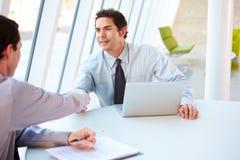 Δύο επιχειρηματίες που διοργανώνουν τη συνεδρίαση γύρω από τον πίνακα στο σύγχρονο γραφείο Στοκ Εικόνες