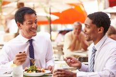 Δύο επιχειρηματίες που διοργανώνουν τη συνεδρίαση στο υπαίθριο εστιατόριο Στοκ Εικόνες