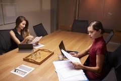 Δύο επιχειρηματίες που κάνουν τη γραφική εργασία αργά σε ένα γραφείο Στοκ Φωτογραφία