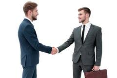 Δύο επιχειρηματίες που κάνουν τη συμφωνία, οι συνάδελφοί τους που στέκεται πλησίον Στοκ φωτογραφίες με δικαίωμα ελεύθερης χρήσης