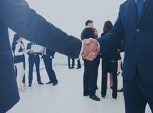 Δύο επιχειρηματίες που κάνουν τη συμφωνία, οι συνάδελφοί τους που στέκεται πλησίον Στοκ φωτογραφία με δικαίωμα ελεύθερης χρήσης