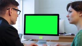 Δύο επιχειρηματίες που μιλούν και που εξετάζουν την επίδειξη υπολογιστών απόθεμα βίντεο