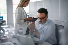 Δύο επιχειρηματίες που προσέχουν κάτι στο lap-top Στοκ Εικόνες