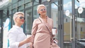 Δύο επιχειρηματίες που στέκονται έξω με τον καφέ με τα κτήρια στο υπόβαθρο φιλμ μικρού μήκους