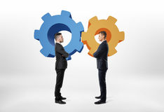 Δύο επιχειρηματίες που στέκονται ο ένας απέναντι από τον άλλον με cogwheel κινούμενων σχεδίων Στοκ Εικόνες