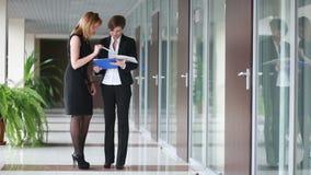 Δύο επιχειρηματίες που συζητούν μια σύμβαση πηγαίνετε γύρω από το γραφείο φιλμ μικρού μήκους