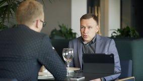 Δύο επιχειρηματίες που συζητούν τα επιχειρησιακά ζητήματα με την ταμπλέτα κατά τη διάρκεια του μεσημεριανού γεύματος απόθεμα βίντεο