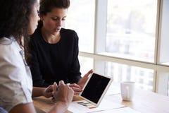 Δύο επιχειρηματίες που χρησιμοποιούν την ψηφιακή ταμπλέτα στη συνεδρίαση των γραφείων Στοκ Εικόνες