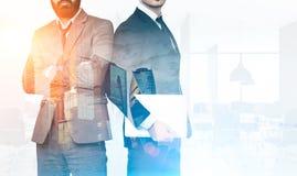 Δύο επιχειρηματίες στην αρχή με τους ουρανοξύστες, που τονίζονται Στοκ φωτογραφία με δικαίωμα ελεύθερης χρήσης