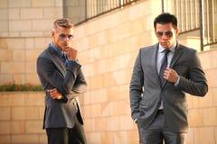 Δύο επιχειρηματίες στο μέτωπο κοντά στον τοίχο, γυαλιά ηλίου Στοκ Εικόνα