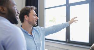 Δύο επιχειρηματίες συζητούν την άποψη παραθύρων στο σύγχρονο coworking διάστημα, ομιλία επιχειρηματιών φυλών μιγμάτων απόθεμα βίντεο
