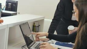 Δύο επιχειρηματίες συζητούν τις πληροφορίες για το lap-top στο γραφείο φιλμ μικρού μήκους