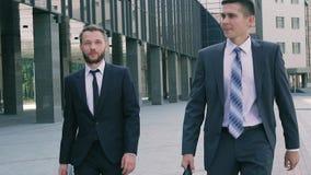 Δύο επιχειρησιακά άτομα που φορούν τα έξυπνα ενδύματα και που κρατούν τις περιπτώσεις δέρματος περπατώντας κατά μήκος του εμπορικ απόθεμα βίντεο
