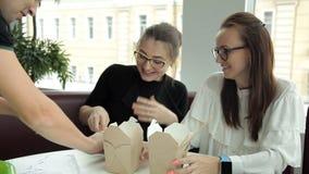 Δύο επιχειρησιακά κορίτσια με τα γυαλιά κάθονται σε έναν καφέ, έφαγαν τα κινεζικά τρόφιμα, ένας σερβιτόρος έρχεται μέχρι τους και απόθεμα βίντεο