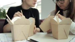 Δύο επιχειρησιακά κορίτσια με τα γυαλιά που κάθονται σε έναν καφέ, που τρώει τα κινεζικά νουντλς στο μεσημεριανό γεύμα Τρόφιμα, κ απόθεμα βίντεο