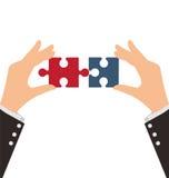 Δύο επιχειρησιακά χέρια που συνδυάζουν δύο κομμάτια του γρίφου ελεύθερη απεικόνιση δικαιώματος