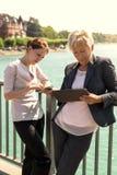 Δύο επιχειρησιακές γυναίκες με την ταμπλέτα και το smartphone που εργάζονται έξω από το θόριο Στοκ φωτογραφία με δικαίωμα ελεύθερης χρήσης
