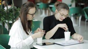 Δύο επιχειρησιακές γυναίκες που συζητούν ένα επιχειρησιακό πρόγραμμα και που πίνουν τον καφέ στον καφέ φιλμ μικρού μήκους