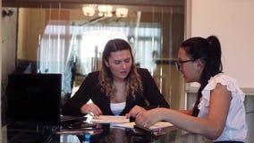 Δύο επιχειρησιακές γυναίκες που συζητούν τις δυσκολίες σε ένα επιχειρησιακό πρόγραμμα σε μια συνεδρίαση γραφείων σε έναν πίνακα H φιλμ μικρού μήκους