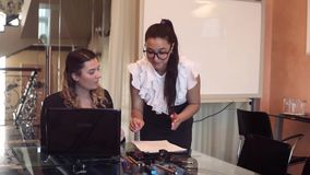 Δύο επιχειρησιακές γυναίκες στα επιχειρησιακά ενδύματα στο γραφείο δοκιμάζουν μια αίσθηση της χαράς και της απόλαυσης μετά από έν απόθεμα βίντεο