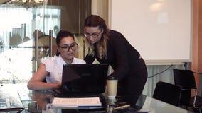 Δύο επιχειρησιακές γυναίκες συζητούν ένα επιχειρησιακό πρόγραμμα στο γραφείο χρησιμοποιώντας έναν υπολογιστή με μια καλή διάθεση απόθεμα βίντεο