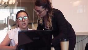 Δύο επιχειρησιακές γυναίκες συζητούν ένα επιχειρησιακό πρόγραμμα στο γραφείο χρησιμοποιώντας έναν υπολογιστή με μια καλή διάθεση  φιλμ μικρού μήκους