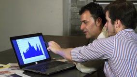 Δύο επιχειρησιακοί συνάδελφοι που συζητούν το διάγραμμα στο lap-top απόθεμα βίντεο