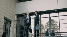 Δύο επιχειρησιακοί συνάδελφοι που χαιρετούν ο ένας τον άλλον στην είσοδο του εμπορικού κέντρου απόθεμα βίντεο