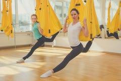 Δύο λεπτά κορίτσια που κάνουν τις ασκήσεις γιόγκας μυγών Στοκ Εικόνα