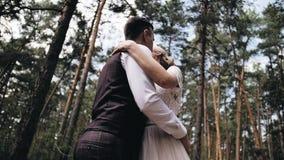 Δύο εραστές αγκαλιάζουν ήπια ο ένας τον άλλον που στέκεται στη μέση ενός όμορφου δάσους πεύκων φιλμ μικρού μήκους