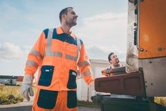 Δύο εργαζόμενοι αποκομιδής απορριμάτων που φορτώνουν τα απορρίματα στο φορτηγό αποβλήτων στοκ εικόνα με δικαίωμα ελεύθερης χρήσης