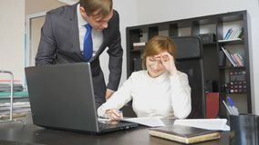 Δύο εργαζόμενοι γραφείων κάθονται στο γραφείο, μια γυναίκα εργάζεται στον υπολογιστή, ένας άνδρας είναι πλησίον Γελούν στοκ φωτογραφία με δικαίωμα ελεύθερης χρήσης