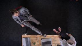 Δύο εργαζόμενοι γραφείων μιλούν, το άτομο βάζει τα πόδια του στο γραφείο, σαμπάνια στον πίνακα, έννοια κομμάτων επιχείρησης, επικ απόθεμα βίντεο