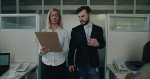 Δύο εργαζόμενοι γραφείων που περπατούν από το γραφείο και που μιλούν μαζί να κοιτάξει μέσω των εγγράφων τους απόθεμα βίντεο