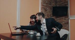 Δύο εργαζόμενοι γραφείων στο χρόνο σπασιμάτων στη διαταγή καφέδων κάτι που χρησιμοποιεί μια πιστωτική κάρτα είναι οι ενθουσιώδεις φιλμ μικρού μήκους