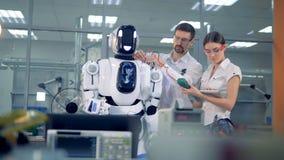 Δύο εργαζόμενοι ελέγχουν την τάση droid ` s απόθεμα βίντεο