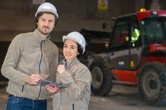 Δύο εργαζόμενοι με την περιοχή αποκομμάτων στη σκοτεινή αποθήκη εμπορευμάτων στοκ εικόνες με δικαίωμα ελεύθερης χρήσης