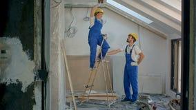 Δύο εργαζόμενοι με τη σκάλα κάνοντας τις επισκευές στην οικοδόμηση απόθεμα βίντεο