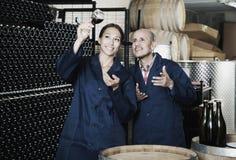 Δύο εργαζόμενοι οινοποιιών που κρατούν το ποτήρι του κρασιού Στοκ εικόνες με δικαίωμα ελεύθερης χρήσης