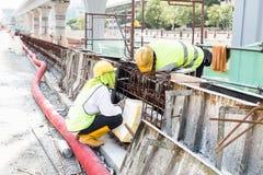 Δύο εργαζόμενοι που εγκαθιστούν την ξύλινη φόρμα επάνω rebar στο εργοτάξιο οικοδομής Στοκ φωτογραφία με δικαίωμα ελεύθερης χρήσης