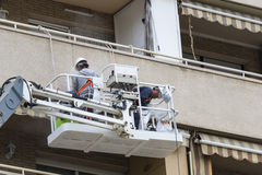 Δύο εργαζόμενοι που επισκευάζουν μια πρόσοψη Στοκ Φωτογραφία