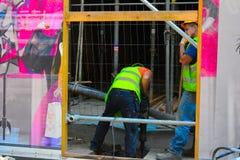 Δύο εργαζόμενοι που τρυπούν την τρύπα Α με τρυπάνι Στοκ εικόνες με δικαίωμα ελεύθερης χρήσης
