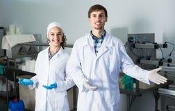 Δύο εργαζόμενοι στα παλτά εργαστηρίων στη γαλακτοκομική παραγωγή Στοκ Εικόνα