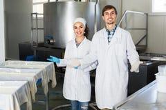 Δύο εργαζόμενοι στα παλτά εργαστηρίων στη γαλακτοκομική παραγωγή Στοκ Εικόνες