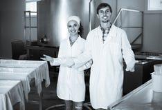Δύο εργαζόμενοι στα παλτά εργαστηρίων στη γαλακτοκομική παραγωγή Στοκ Φωτογραφίες
