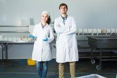 Δύο εργαζόμενοι στα παλτά εργαστηρίων στη διαδικασία παραγωγής Στοκ Φωτογραφία