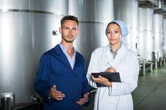 Δύο εργαζόμενοι στα παλτά στην οινοποιία manufactory Στοκ Εικόνες
