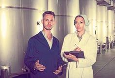 Δύο εργαζόμενοι στα παλτά στην οινοποιία manufactory Στοκ Φωτογραφία