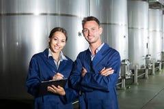 Δύο εργαζόμενοι στα παλτά στην οινοποιία manufactory Στοκ φωτογραφία με δικαίωμα ελεύθερης χρήσης